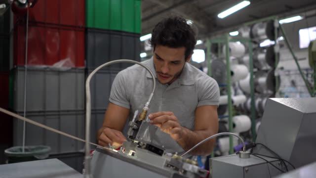 männliche ingenieur-kalibriermaschine in einer gummibandfabrik - qualitätsprüfer stock-videos und b-roll-filmmaterial