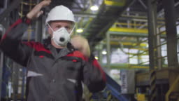 Male Engineer in Hardhat and Respirator Walking along Production Line