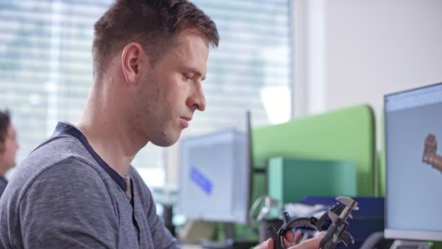 vidéos et rushes de ds ingénieur mâle prenant des mesures d'un composant à son bureau - mesurer