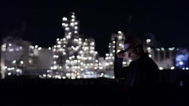 ms male engineer mit digitalem tablet in beleuchteter ölraffinerie in der nacht - hingabe stock-videos und b-roll-filmmaterial