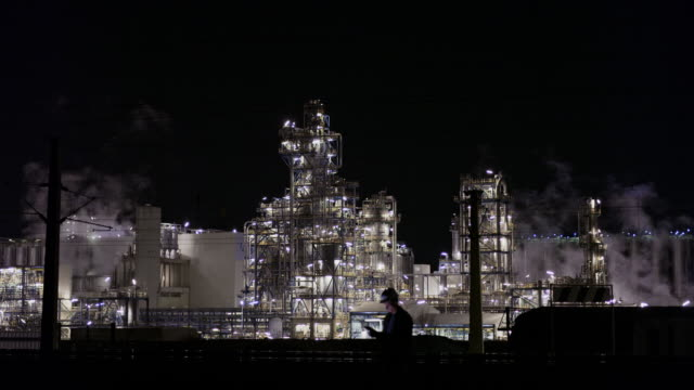 vídeos de stock e filmes b-roll de ws male engineer using digital tablet at illuminated oil refinery at night - indústria petrolífera
