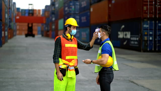 male engineer wearing protective face mask and spraying alcohol to worker's hand before start working in a commercial shipping dock during coronavirus crisis - shipping stock videos & royalty-free footage