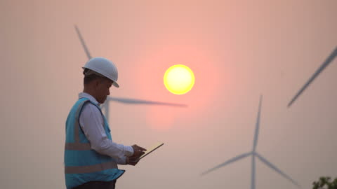 male engineer with digital tablet in front of wind turbines - wind turbine stock videos & royalty-free footage