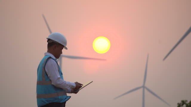 male engineer with digital tablet in front of wind turbines - windmill stock videos & royalty-free footage