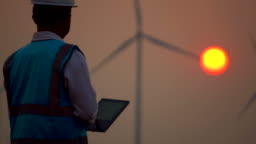 Male engineer with digital tablet in front of wind turbines