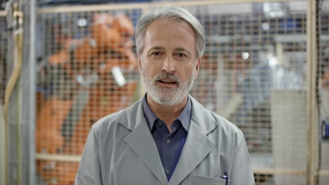 männliche ingenieur mit grauem haar und bart bei einem videoanruf aus einer fabrik - ingenieur stock-videos und b-roll-filmmaterial