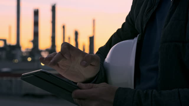 cu male engineer with hardhat using digital tablet at refinery at dusk - refinery stock videos & royalty-free footage