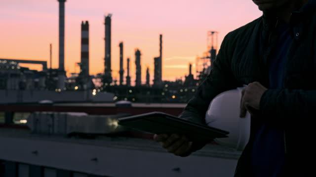 ms male engineer mit hardhat mit digitalem tablet in der raffinerie in der dämmerung - hingabe stock-videos und b-roll-filmmaterial