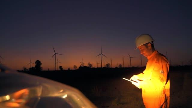 männlicher ingenieur arbeitet in windkraftanlagen farm, zeitlupe. - generator stock-videos und b-roll-filmmaterial