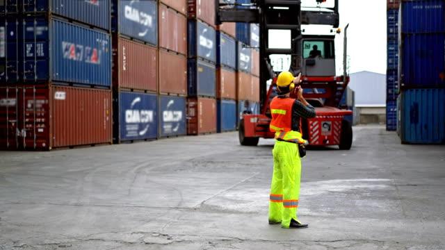 stockvideo's en b-roll-footage met mannelijke ingenieur die met een vorkheftruck werkt die stapelcontainers in een commercieel scheepvaartdok verplaatst - bouwmachines