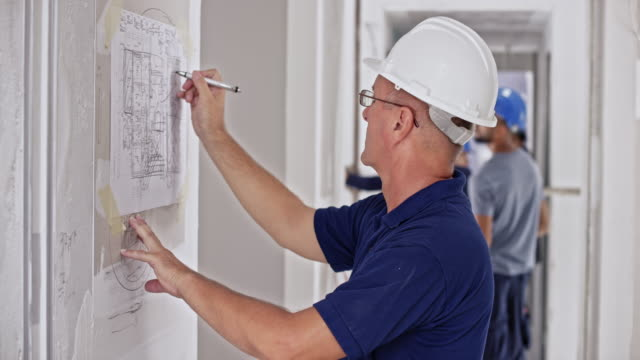 male engineer writing on the plan hanging on the board at the building site - hanging stock videos & royalty-free footage