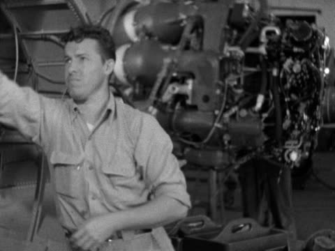 Male engineering connecting wires to engine fuselage parts in hangar workers working on large engine on crane BG War effort production US Navy...
