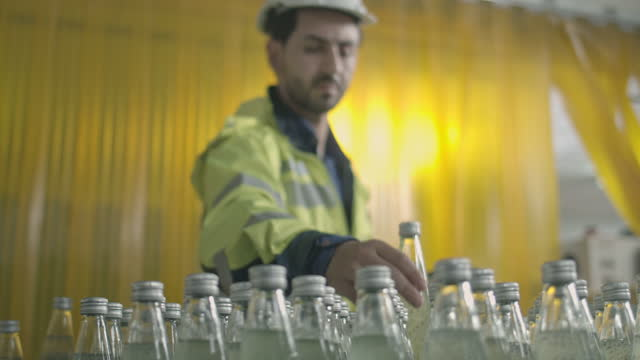 male engineering wearing safty uniform checking the bottles in row on conveyor belt - quality control stock videos & royalty-free footage