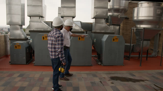 male engineers inspecting air ducts at a rooftop of a hospital wearing protective face masks and helmet - air duct stock videos & royalty-free footage