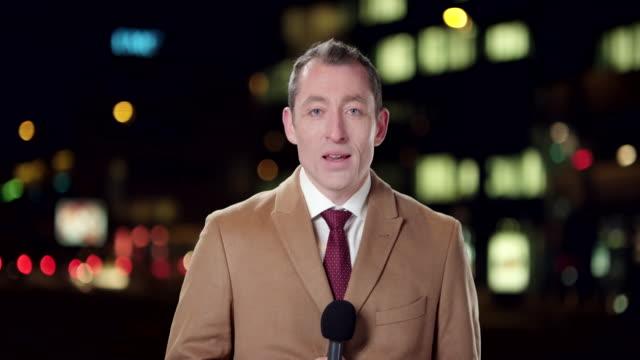 stockvideo's en b-roll-footage met mannelijke engels verslaggever rapportage live vanuit de stad bij nacht - live evenement