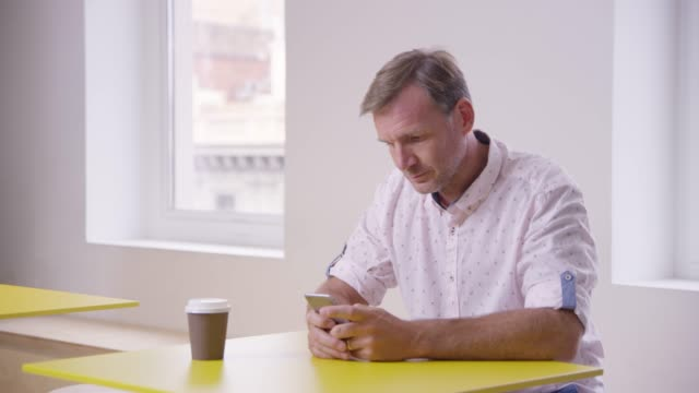 Male entrepreneur text messaging on smart phone