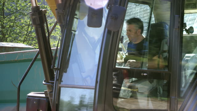 male excavator operator working at a construction site - construction vehicle stock videos & royalty-free footage