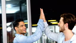 Male executives giving high-five to each other