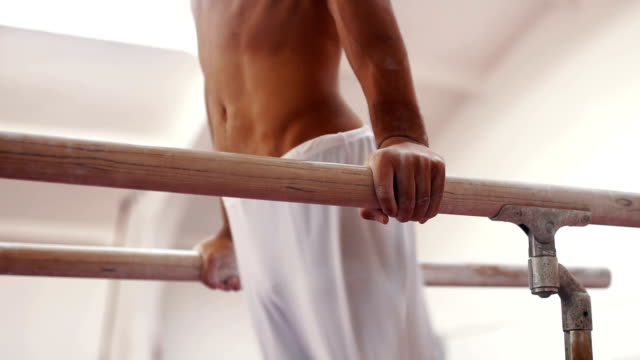 Male exercising on parallel bars