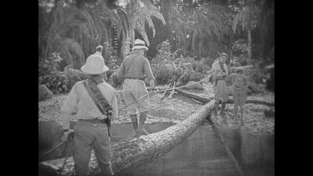 1925 male explorer stops to pick up insect while crossing tree bridge - 1925 stock videos & royalty-free footage