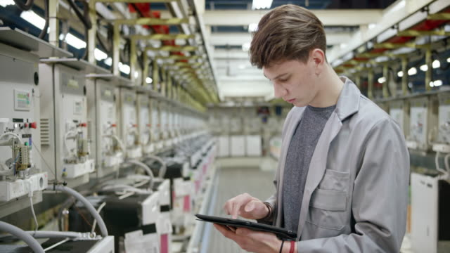 male factory employee checking the data on the screens of the machines doing product testing and using a digital tablet - industry stock videos & royalty-free footage