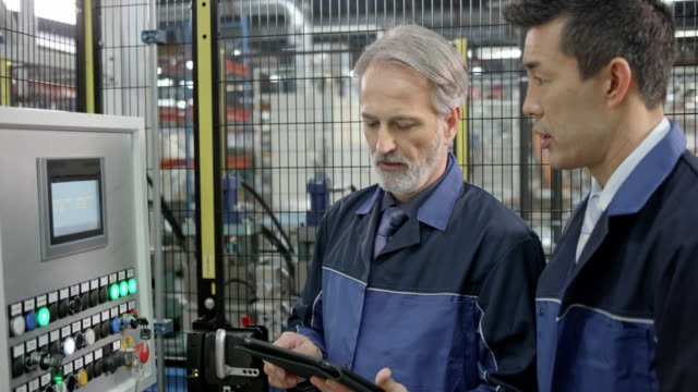 male factory employee reading data from the tablet and comparing it with data on a touch screen lcd while discussing it with male coworker - machinery stock videos & royalty-free footage