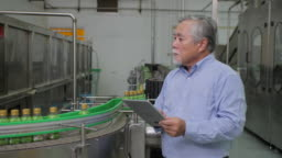 A male factory manager in beverages manufacturing industry looking at computer tablet and checking the quality of the product. Production of drinking water and beverages
