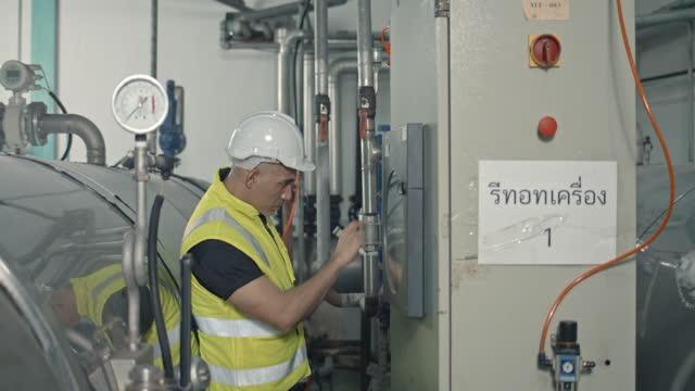 vídeos y material grabado en eventos de stock de trabajador de fábrica masculino usa sombrero duro de seguridad y uniforme usando computadora portátil para revisar la máquina - un solo hombre maduro