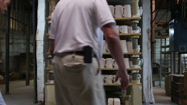 male factory workers push rack into kiln - kiln stock videos and b-roll footage