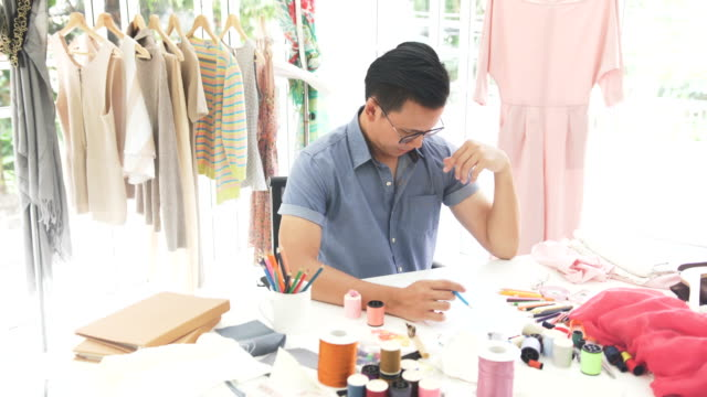male fashion designer design and write the model in home office - 30 34 years video stock e b–roll