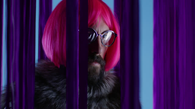 male fashion model in pink wig and eyeglasses, wearing silver fox fur. fashion video. - drag queen stock videos and b-roll footage