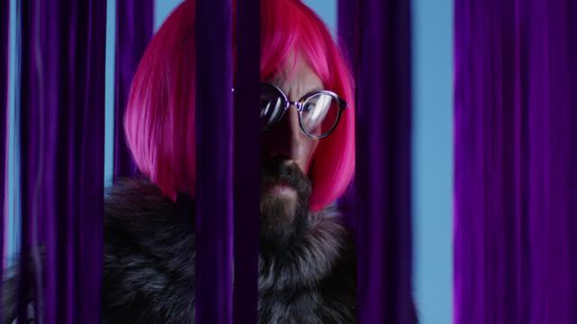Male fashion model in pink wig and eyeglasses, wearing silver fox fur. Fashion video.