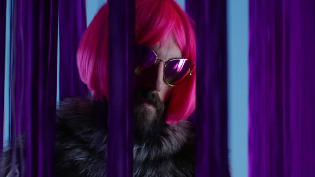 stockvideo's en b-roll-footage met mannelijke mannequin in roze pruik en zonnebrillen, silver fox bont te dragen. video mode. - pruik