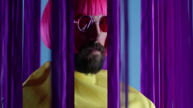 stockvideo's en b-roll-footage met mannelijke mannequin in roze pruik en zonnebril, het dragen van gele jas. video mode. - pruik