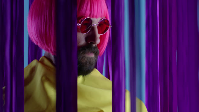 male fashion model in pink wig and sunglasses, wearing yellow coat. fashion video. - fashion stock videos & royalty-free footage