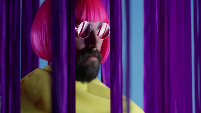 Male fashion model in pink wig and sunglasses, wearing yellow coat. Fashion video.