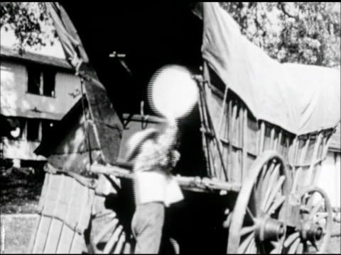 male, father loading large wooden barrel into conestoga covered wagon, attaching back panel. - westward expansion stock videos & royalty-free footage
