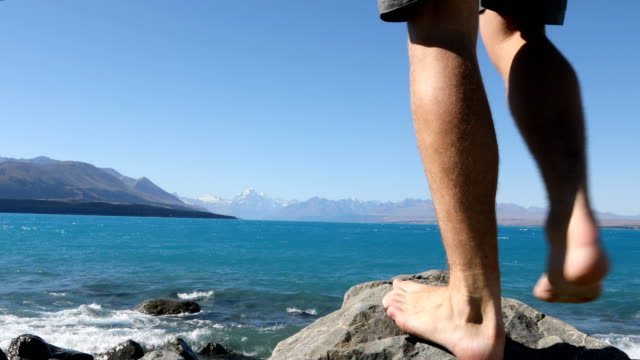 male feet step up onto rock at lake pukaki with view of distant mount cook - scalzo video stock e b–roll