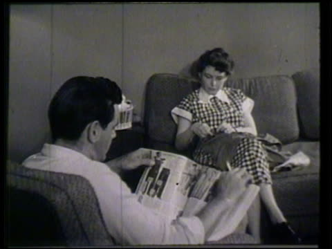 Male female couple sitting in living room male reading mail order catalog female sewing MCU Male hands flipping through catalog clothing section...