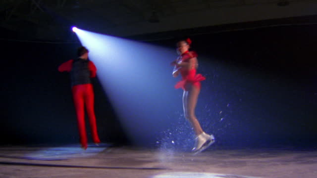 PAN male + female figure skaters skating + doing twisting jumps in unison in spotlight