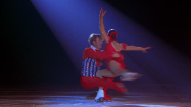 male + female figure skaters with legs out in pose spinning together in spotlight - figure skating stock videos and b-roll footage