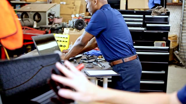 Male, female mechanics working together in auto repair shop.