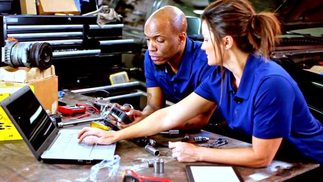 vídeos y material grabado en eventos de stock de taller de reparaciones de mecánica masculina, femenina, trabajando juntos en el auto. - mecánico de coches