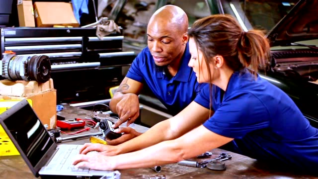 male, female mechanics working together in auto repair shop. - repair shop stock videos & royalty-free footage