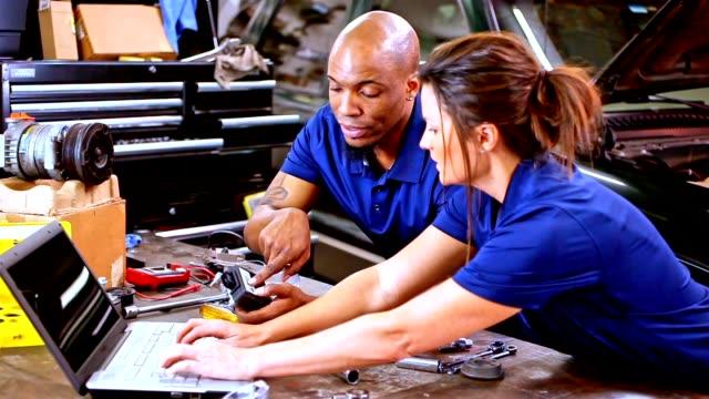 male, female mechanics working together in auto repair shop. - laboratorio riparazioni video stock e b–roll