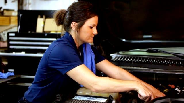stockvideo's en b-roll-footage met mannelijke, vrouwelijke mechanica werken samen in de auto reparatiewerkplaats. - latin american and hispanic ethnicity