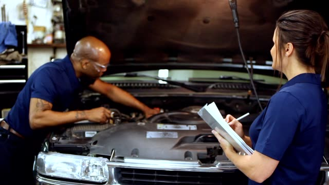 male, female mechanics working together in auto repair shop. - minority groups stock videos and b-roll footage