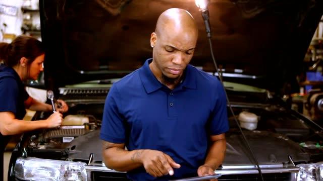 vídeos de stock, filmes e b-roll de masculina, feminina mecânica trabalhando juntos em auto oficina. - prancheta