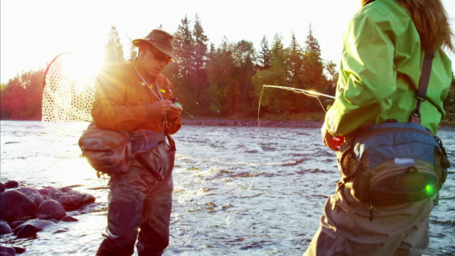 Male female rod and reel fishing in river