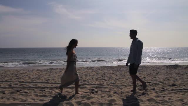vidéos et rushes de male & female walk toward each other and kiss on beach - affectueux